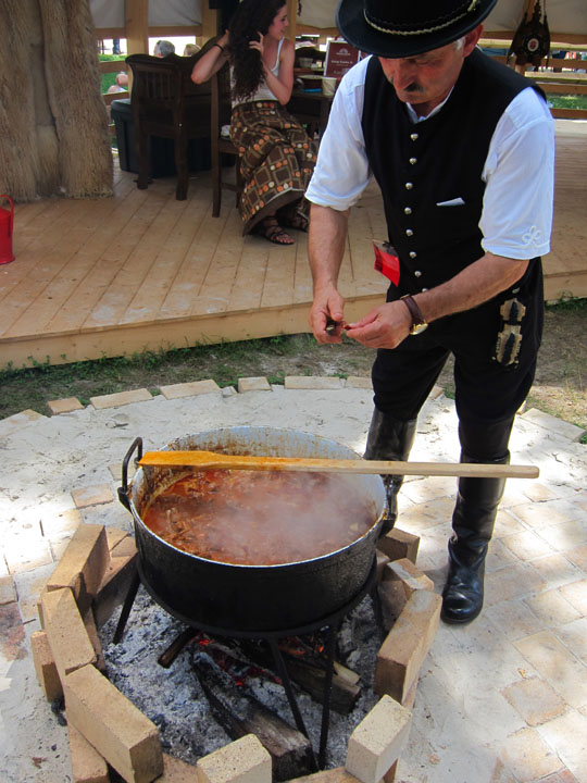 chef adjusts, Hungarian Cauldron cooking