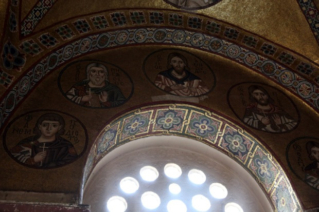 Window frames in mosaic roundels of saints.