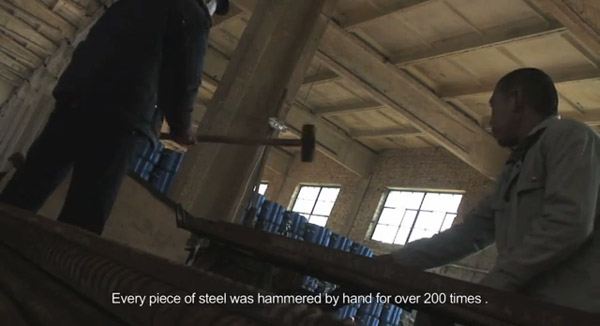 Workers straightened each piece of rehar by hand. (Screen capture from the video above.)