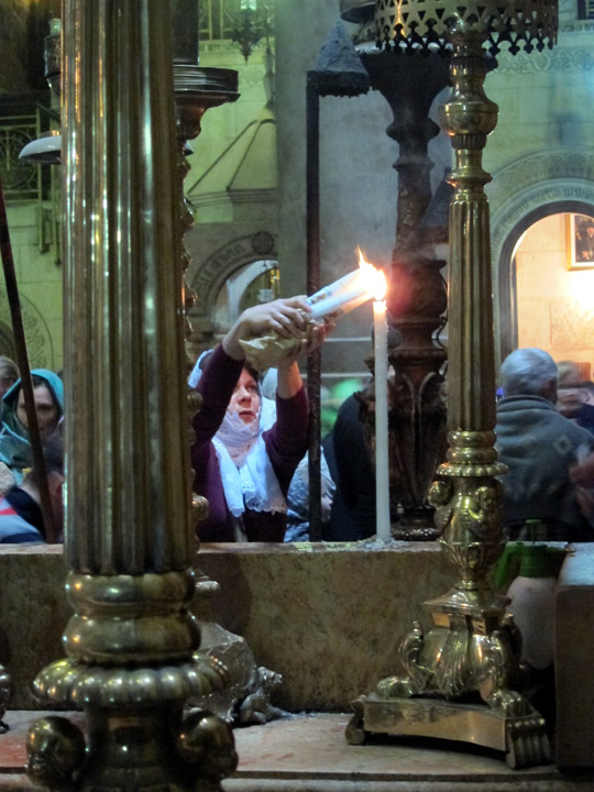 Orthodox pilgrim lighting candles at the Holy Sepulchre