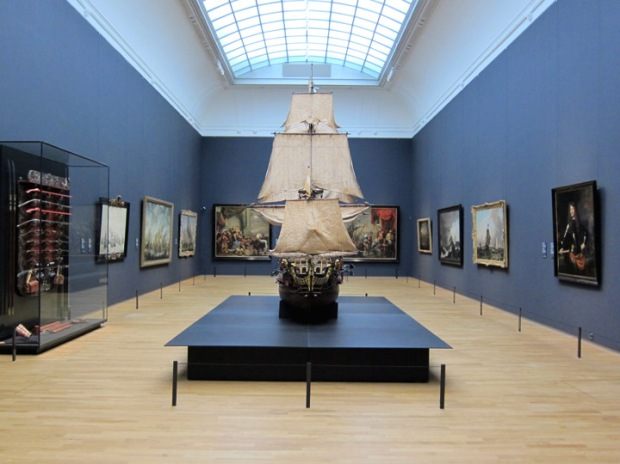 A massive ship model with maritime paintings.