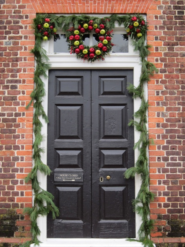 A festive door decorated with apples.